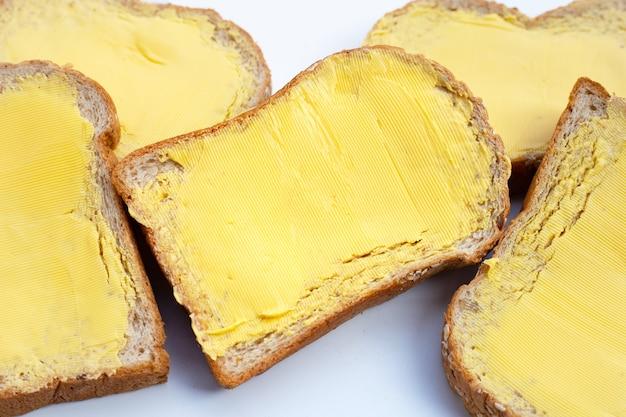 Fatias de pão com manteiga em fundo branco.