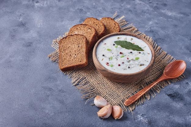 Fatias de pão com uma xícara de sopa de iogurte e alho.