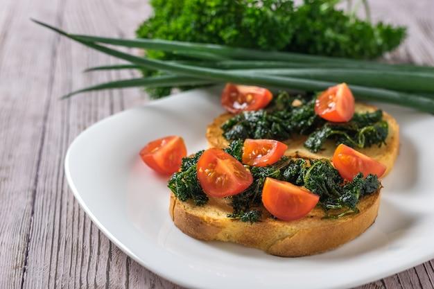 Fatias de pão com verduras fritas e fatias de tomate em uma mesa de madeira. lanche vegetariano.