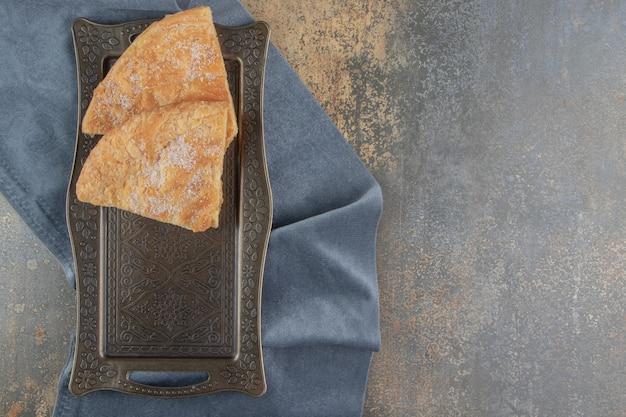 Fatias de pão crocante em uma pequena bandeja ornamentada em madeira.