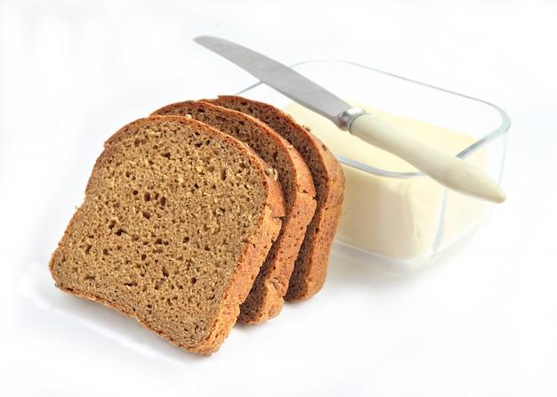Fatias de pão de centeio e manteiga em um recipiente de vidro