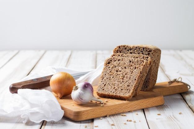 Fatias de pão de espelta com cebola e alho caem na mesa da cozinha, sobre um fundo claro de madeira.