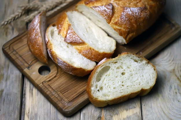 Fatias de pão de trigo fresco em uma superfície de madeira