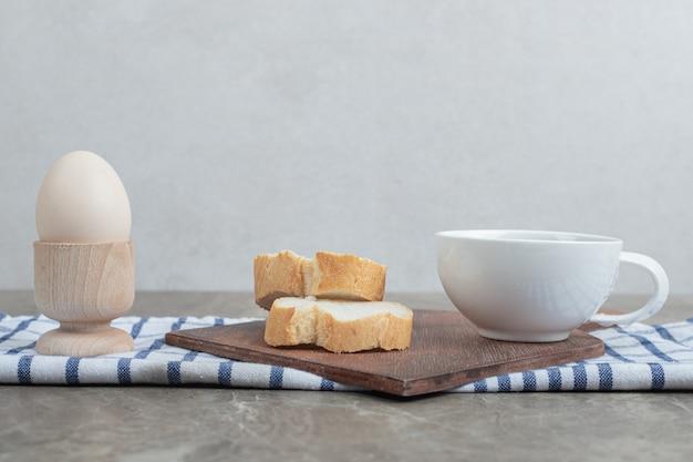 Fatias de pão e chá na placa de madeira com ovo. foto de alta qualidade