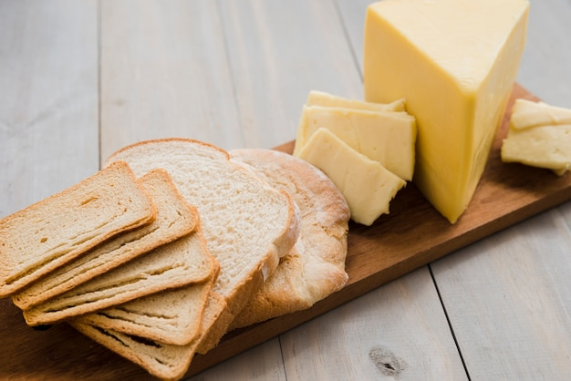 Fatias de pão e fatias de queijo na tábua sobre a mesa