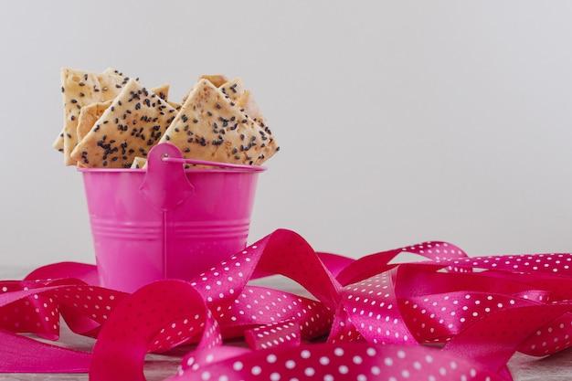 Fatias de pão em um pequeno balde ao lado de um feixe de fitas no mármore Foto gratuita