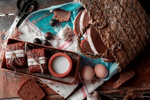 Fatias de pão embrulhadas com papel branco e linha, pote de leite dentro de um boc, cesta ao redor. vista superior.