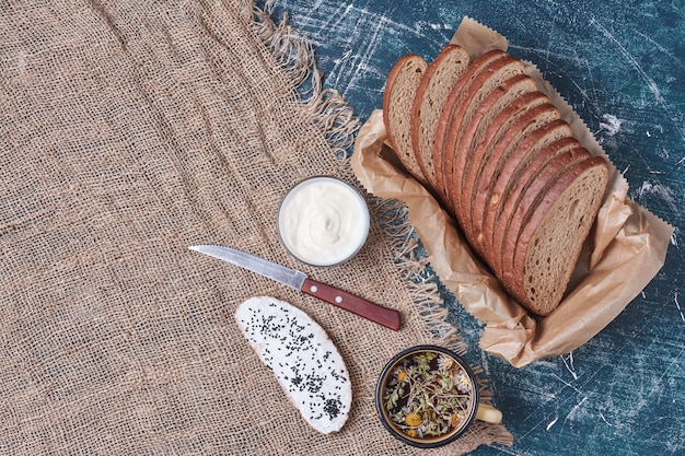 Fatias de pão escuro na bandeja de madeira com torradas e bebidas.