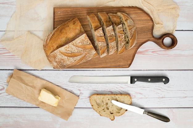 Fatias de pão; faca; manteiga no papel e butterknife na mesa de madeira