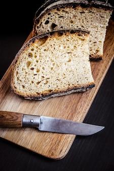 Fatias de pão francês tradicional e canivete em uma tábua de madeira. vista do topo