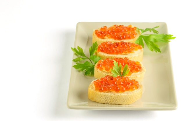 Fatias de pão fresco branco aplicadas com manteiga e caviar vermelho. isolado no fundo branco.