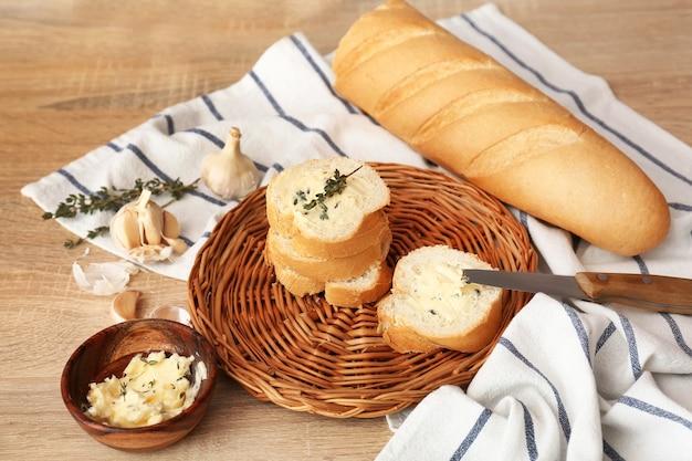 Fatias de pão fresco com manteiga, ervas e alho na mesa