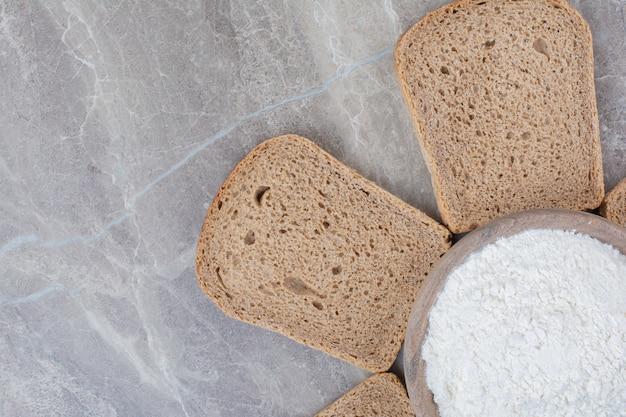 Fatias de pão integral com farinha na superfície de mármore