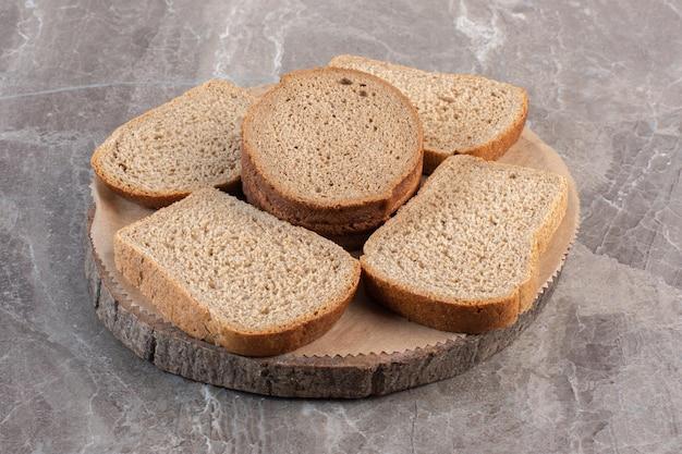 Fatias de pão integral em uma placa de madeira com fundo de mármore. foto de alta qualidade