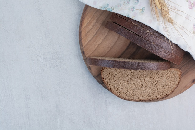 Fatias de pão integral fresco na placa de madeira.