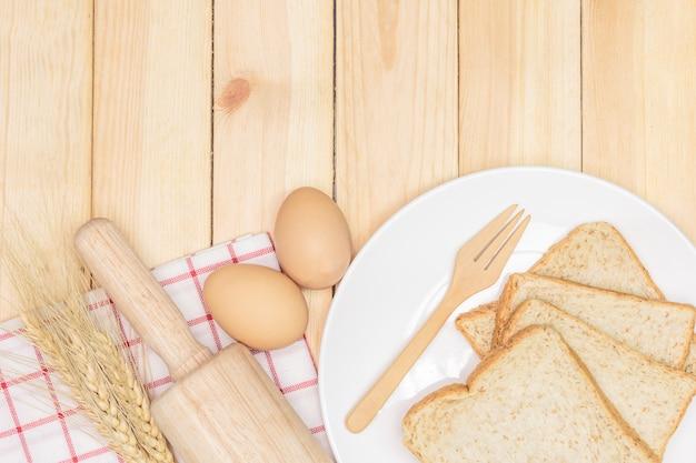 Fatias de pão integral na chapa branca com espigas de trigo e ovo no fundo da mesa de madeira