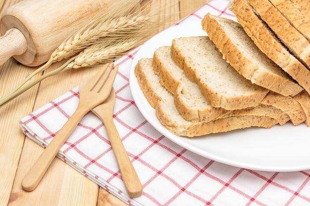 Fatias de pão integral na chapa branca com espigas de trigo no fundo da mesa de madeira