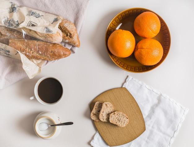 Fatias de pão; laranjas inteiras; xícara de chá e leite em pó no fundo branco