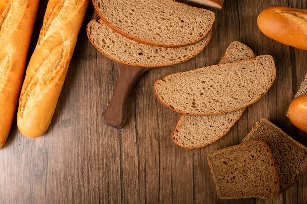 Fatias de pão marrom e branco na placa da cozinha com baguete