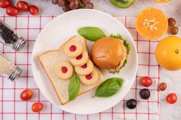 Fatias de pão, pães recheados e hambúrgueres em um prato branco.