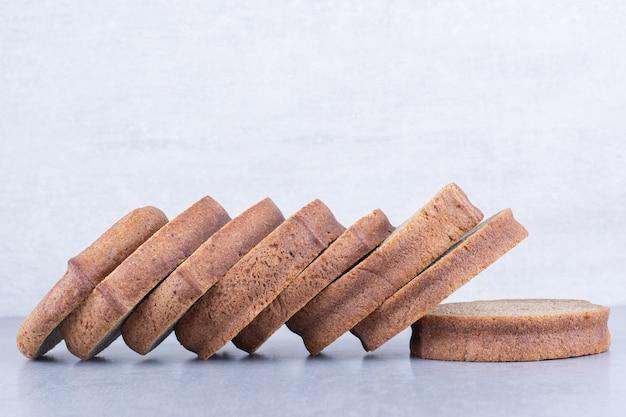 Fatias de pão preto alinhadas na superfície de mármore