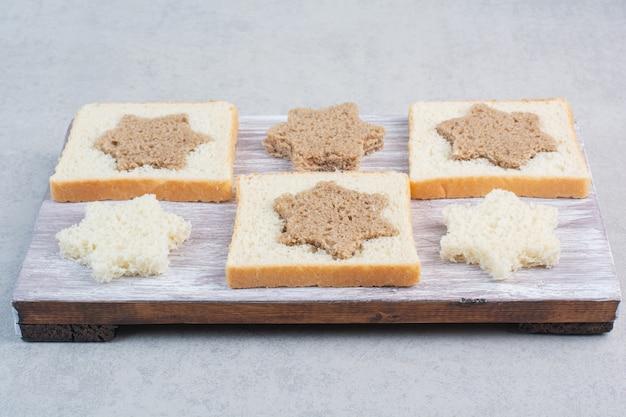 Fatias de pão preto e branco em formato de estrela e quadrada em um prato de madeira