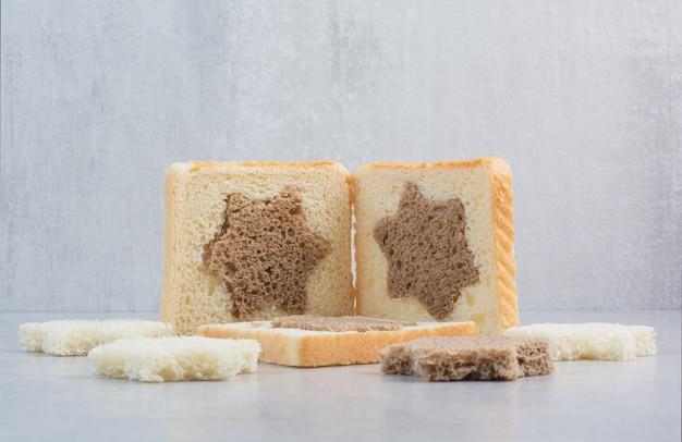 Fatias de pão preto e branco em formato de estrela e quadrada na mesa de pedra