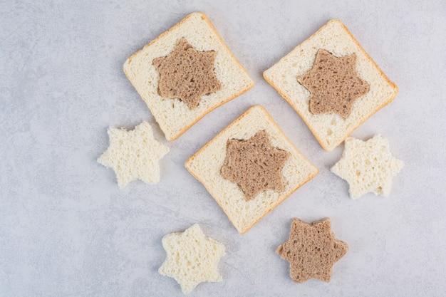 Fatias de pão preto e branco em formato de estrela e quadrada na superfície da pedra