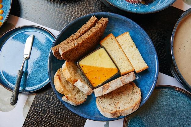 Fatias de pão preto e branco em uma tigela com molho e faca