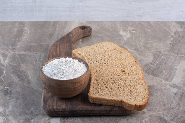 Fatias de pão preto e uma tigela de farinha em uma placa sobre fundo de mármore. foto de alta qualidade