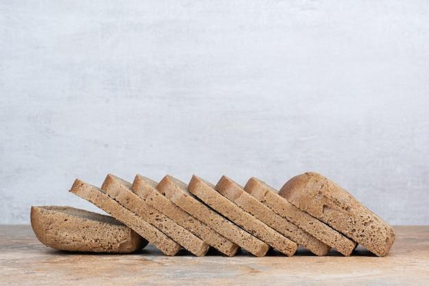 Fatias de pão preto na mesa de mármore
