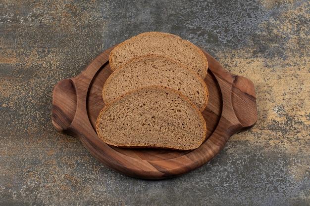 Fatias de pão preto saboroso na placa de madeira.