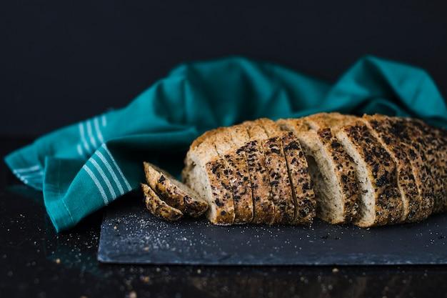Fatias de pão saudável em ardósia perto do guardanapo contra fundo preto