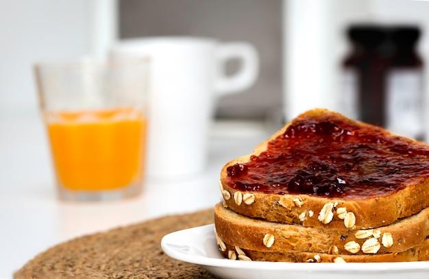 Fatias de pão torrada com geléia de morango caseira no café da manhã com fundo desfocado