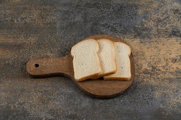 Fatias de pão torrado branco na tábua de madeira