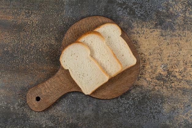 Fatias de pão torrado branco na tábua de madeira.