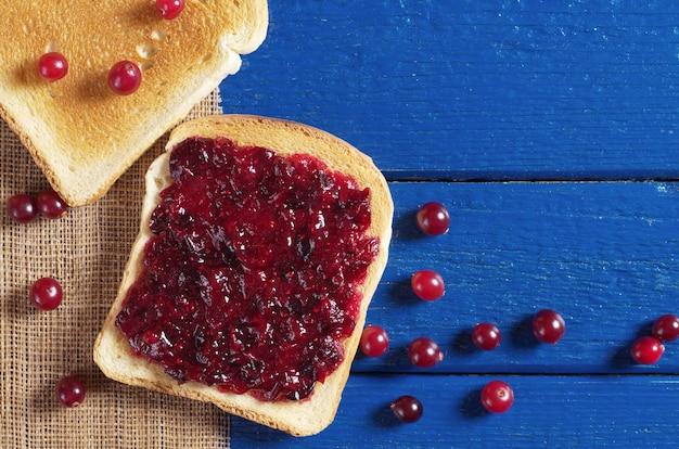 Fatias de pão torrado com geleia de cranberry e frutas vermelhas na mesa de madeira azul