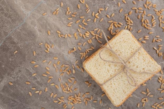 Fatias de pão torrado com grãos na superfície de mármore. foto de alta qualidade
