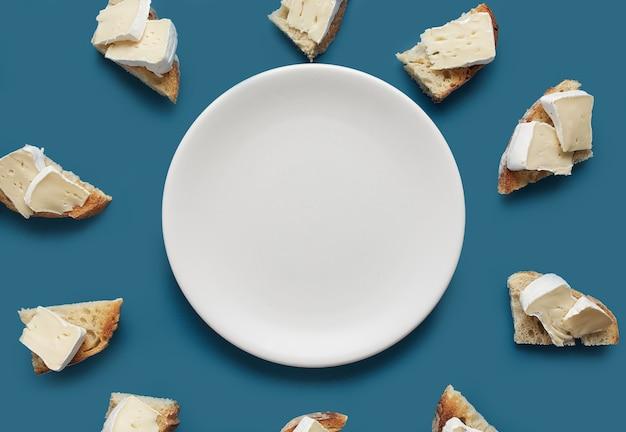 Fatias de pão torrado com queijo brie e prato branco sobre fundo azul escuro, vista de cima