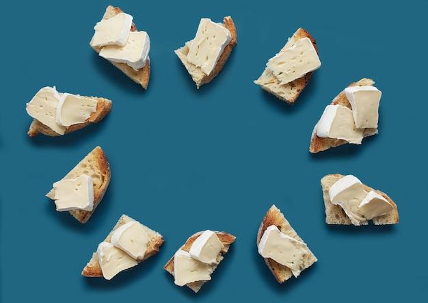 Fatias de pão torrado com queijo brie em fundo azul escuro, vista de cima