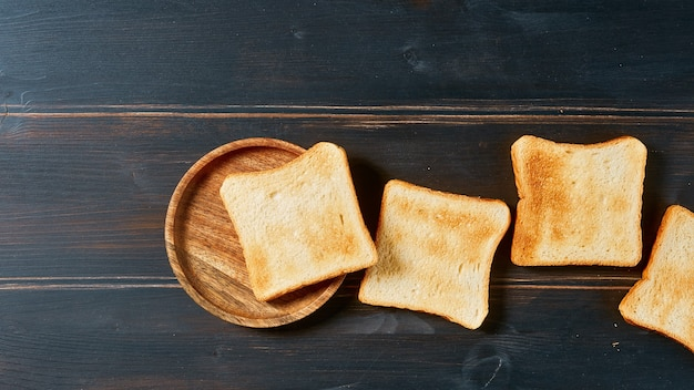 Fatias de pão torrado em mesa de madeira rústica, vista de cima