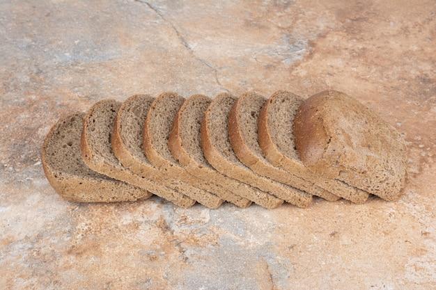 Fatias de pão torrado preto sobre fundo de mármore