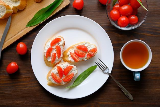 Fatias de pão, uma caneca de chá, sanduíches com queijo e tomate, folhas de salada verde em uma mesa de madeira. o conceito de produtos agrícolas orgânicos no café da manhã ou lanche, vegetarianismo. fechar-se.