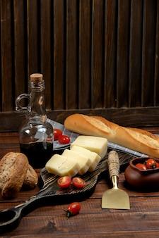 Fatias de parmesão servidas na tábua de madeira servida com baguete