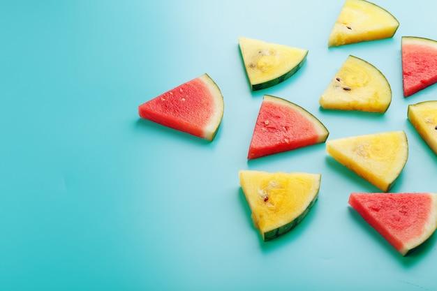 Fatias de pedaços frescos de melancia amarela e vermelha em um azul. lugar livre.