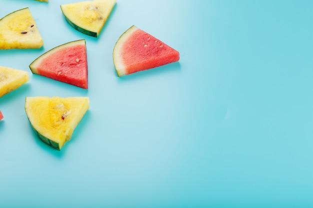 Fatias de pedaços frescos de melancia amarela e vermelha no azul.