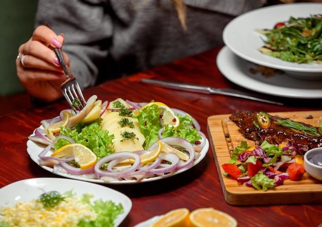 Fatias de peixe com ervas cebolas e limões