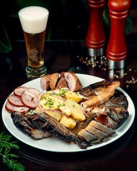 Fatias de peixe defumado e batatas com cerveja