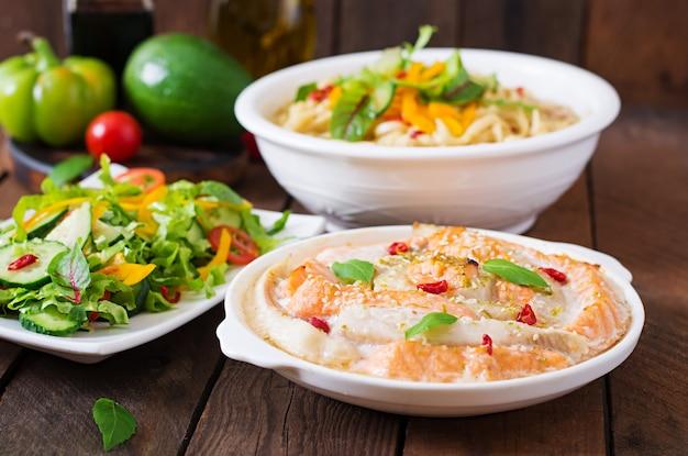 Fatias de peixe vermelho e branco assadas com mel e suco de limão, servidas com salada fresca e macarrão macio em caldo de missô