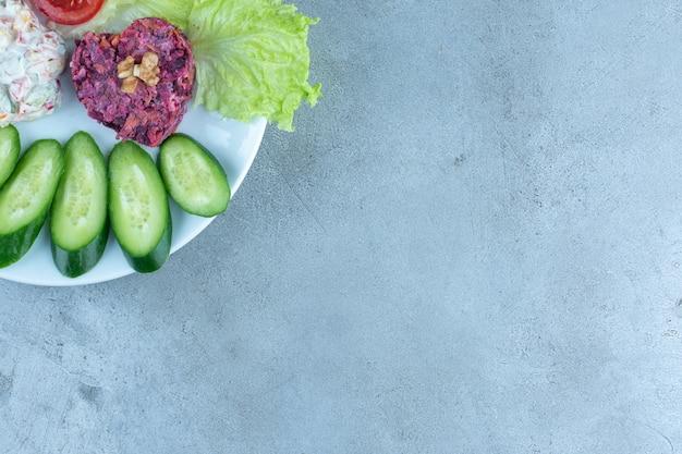 Fatias de pepino e tomate com alface enfeitando duas saladas em uma travessa na mesa de mármore.